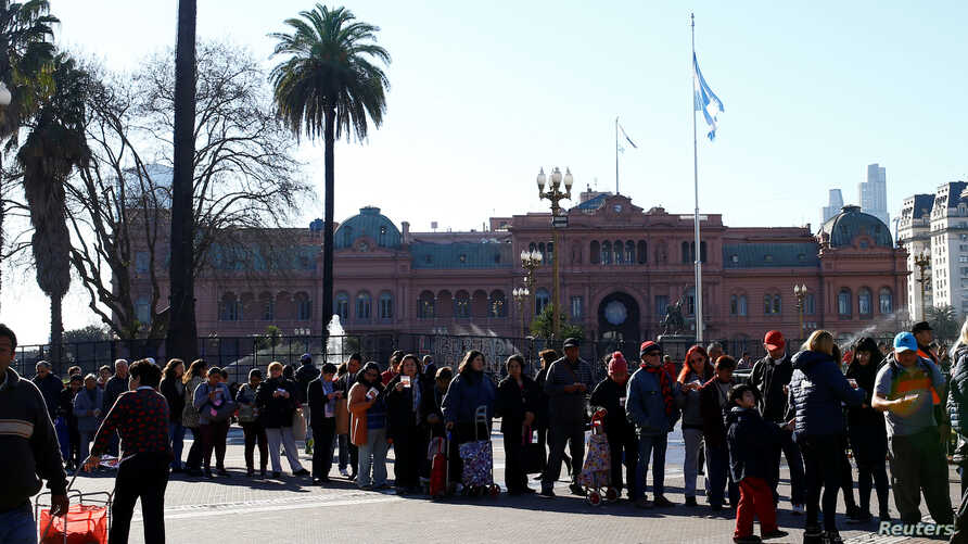 People line up in front of the Casa Rosada Government House to receive free pears and apples during a protest staged by Argentine producers and farmers from the Patagonian provinces of Neuquen and Rio Negro for their losses in Buenos Aires, Argentina