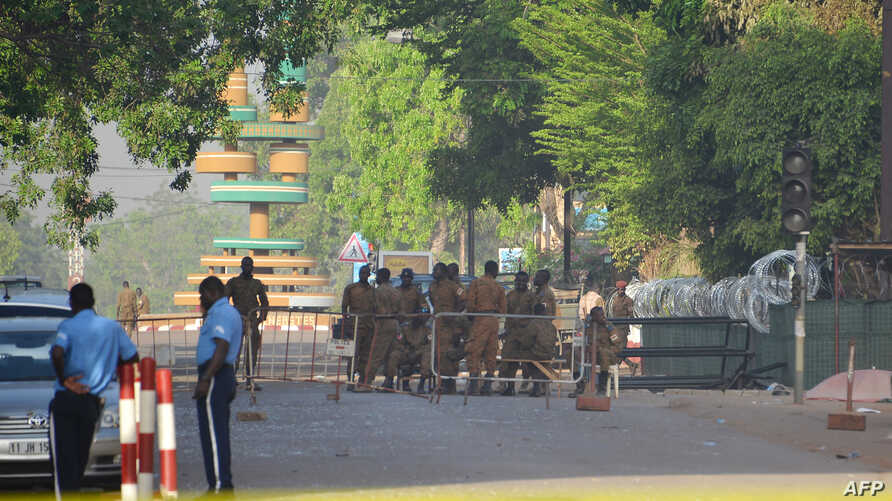 Military personnel stand outside the headquarters of the country's defence forces in Ouagadougou on March 3, 2018 a day after dozen of people were killed in twin attacks on the French embassy and the country's military.