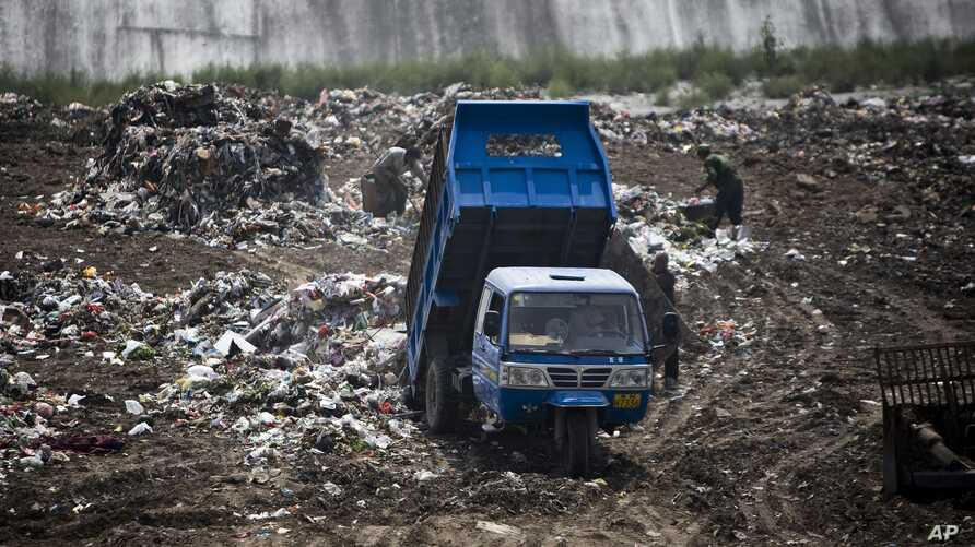 FILE - A garbage truck dumps trash at a site near a village in Zhanglidong, Henan province, China, Sept. 1, 2009.