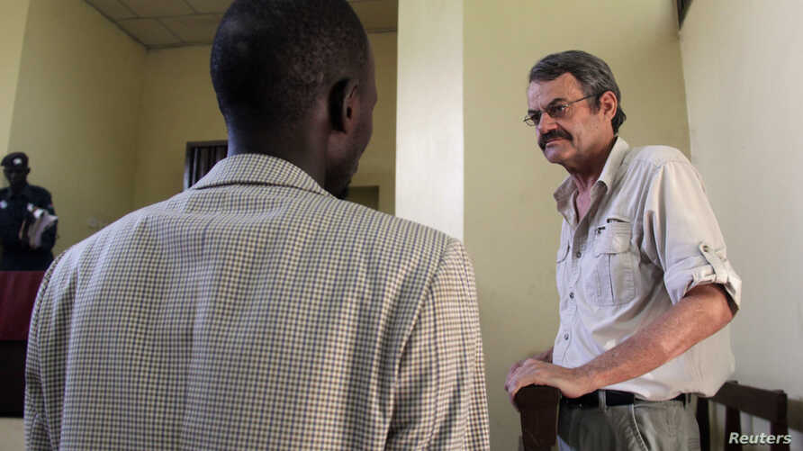 William John Endley, a South African national and an adviser to South Sudanese rebel leader Riek Machar, stands inside the dock in the High Court as his lawyer Gar Adel Gar looks on, in Juba, South Sudan, Feb. 13, 2018.