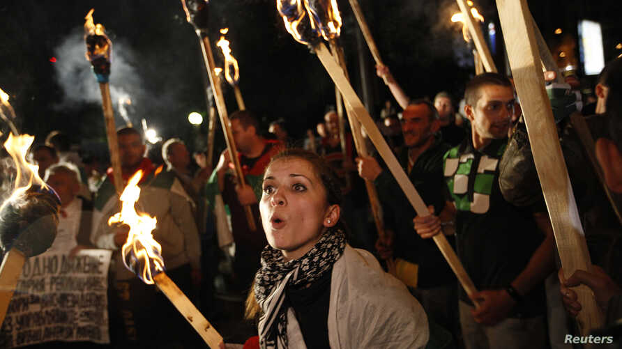 A protester shouts slogans near others holding torches during a demonstration outside the National Palace of Culture, where the political parties in the elections will be holding news conferences, in Sofia, May 12, 2013.