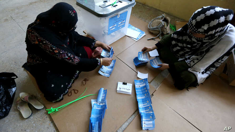Afghan election workers count ballots in the presidential runoff at a polling station in Jalalabad, east of Kabul, Afghanistan, June 14, 2014.