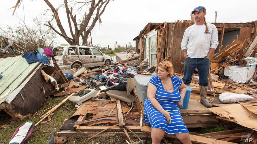 Raella Faulkner, at left, and Bobby McElroy survey what's left of their home, April 28, 2014, after a tornado struck the town of Vilonia, Arkansas late Sunday.