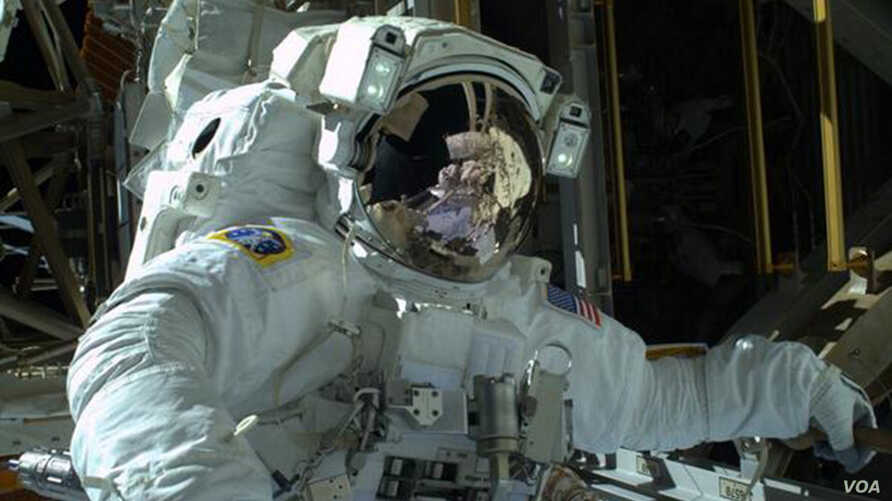 NASA astronaut Mike Hopkins is seen during the spacewalk in this photo courtesy of NASA, received December 22, 2013.  Two NASA astronauts, their spacesuits rigged with snorkels in case of a water leak, floated outside the International Space Station