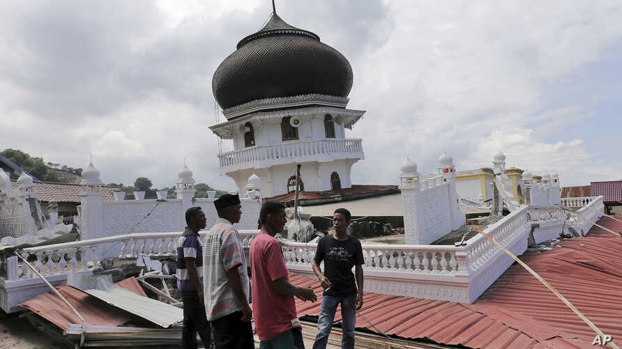 Men inspect a collapsed mosque after an earthquake in Pidie Jaya, Aceh province, Indonesia, Dec. 7, 2016. A strong undersea earthquake rocked Indonesia's Aceh province early Wednesday, killing a number of people and causing dozens of buildings to co
