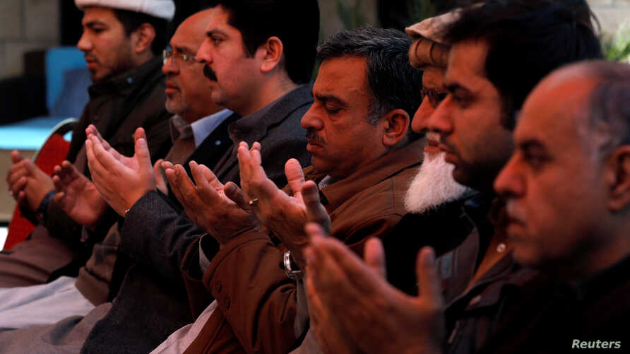 Relatives and family members of Naeem Rashid who was killed along with his son Talha Naeem in the Christchurch mosque attack in New Zealand, pray during a condolence gathering at the family's home in Abbottabad, Pakistan, March 17, 2019.