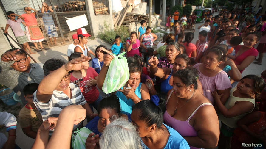 FILE - People queue to receive food donations after an earthquake that struck on the southern coast of Mexico late on Thursday, in Juchitan, Mexico, Sept. 9, 2017.