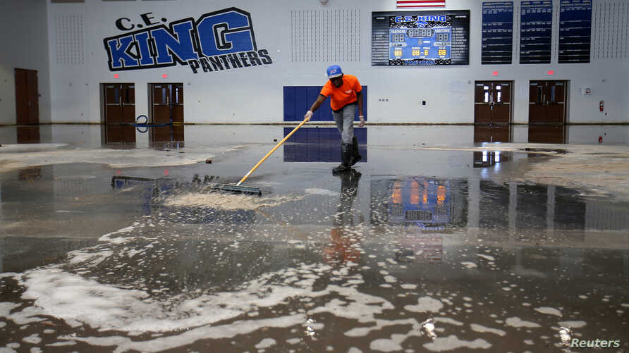 Darius Moses works removing water from the gymnasium at C.E. King High School following the aftermath of tropical storm Harvey in Houston, Texas, Sept. 8, 2017.