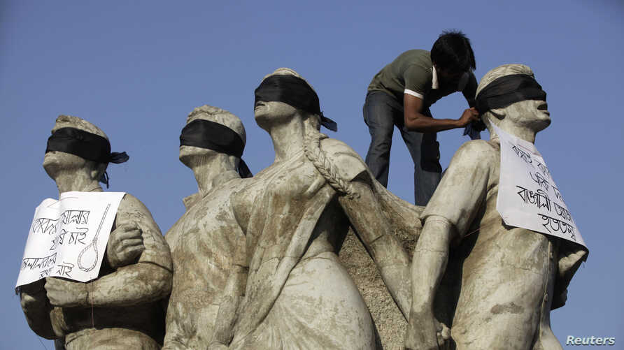 A student activist puts black scarves on the eyes of Shoparjito Shadhinota, a sculpture that represented all sections of people in Bangladesh's liberation War in 1971, demanding capital punishment for Bangladesh's Jamaat-e-Islami senior leader Abdul