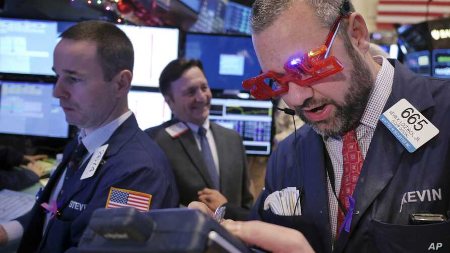 A trader wears glasses in the shape of 2015 while working on the floor at the New York Stock Exchange in New York, Dec. 31, 2014.