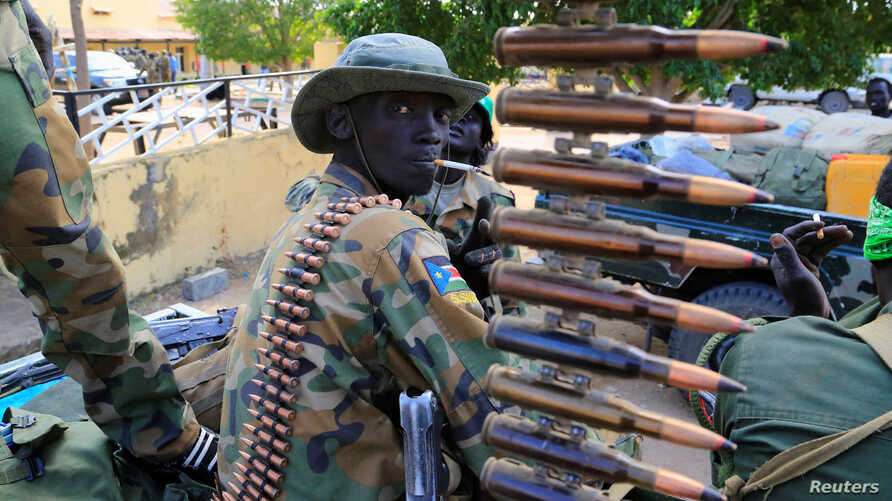 FILE - A South Sudanese soldier stands next to a machine gun mounted on a truck in Malakal town, northeast of Juba, South Sudan.