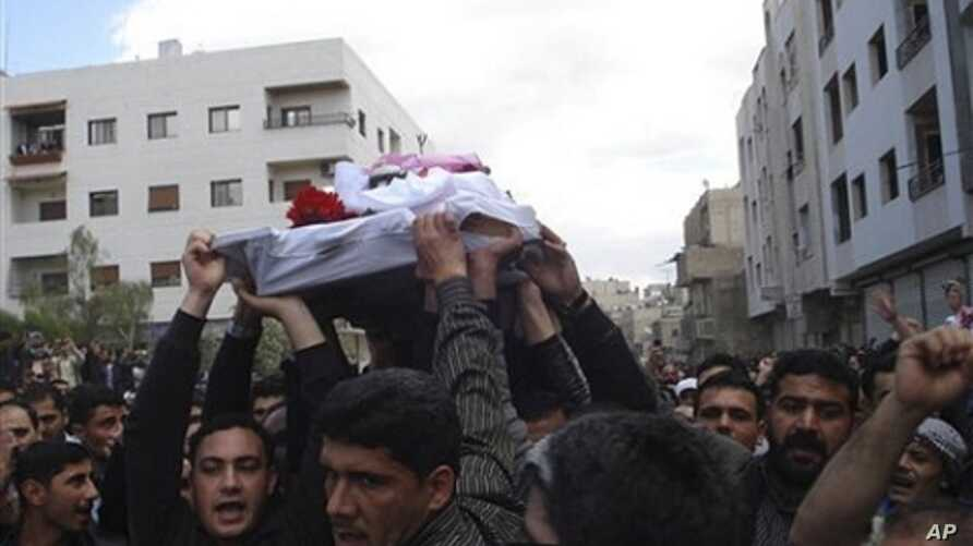 In this citizen journalism image made on a mobile phone and acquired Saturday April 23, 2011, by The AP, Syrian anti-government protesters carry the coffin of an activist who was killed on Friday during his funeral procession in Quaboun near Damascus