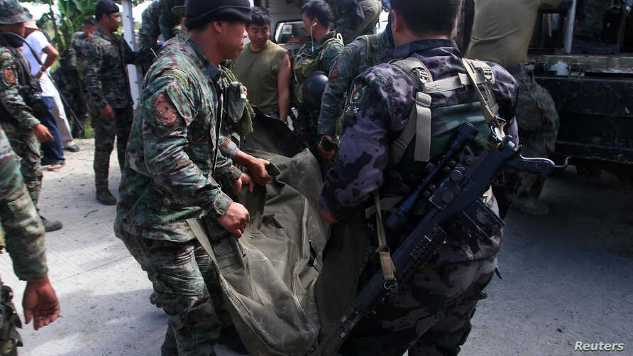 Philippine National Police (PNP) carry a body bag, containing a member of the Special Action Force, to a van in Mamasapano town, Maguindanao province, January 26, 2015.