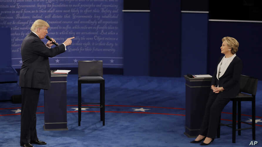 FILE - Then Republican presidential nominee Donald Trump speaks to then Democratic presidential nominee Hillary Clinton during the second presidential debate at Washington University in St. Louis, Missouri, Oct. 9, 2016.
