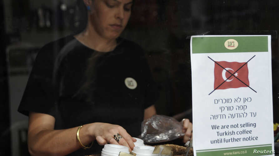 FILE - An employee stands behind a sign depicting a crossed out Turkish flag taped to the window of a coffee shop in Tel Aviv, Oct. 27, 2009.