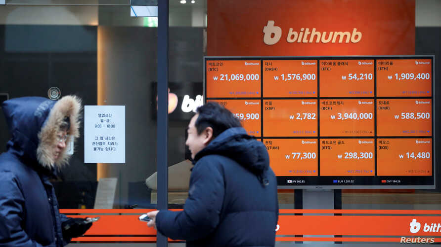 Men talk in front of an electric board showing exchange rates of various cryptocurrencies at Bithumb cryptocurrencies exchange in Seoul, South Korea, Jan. 11, 2018.