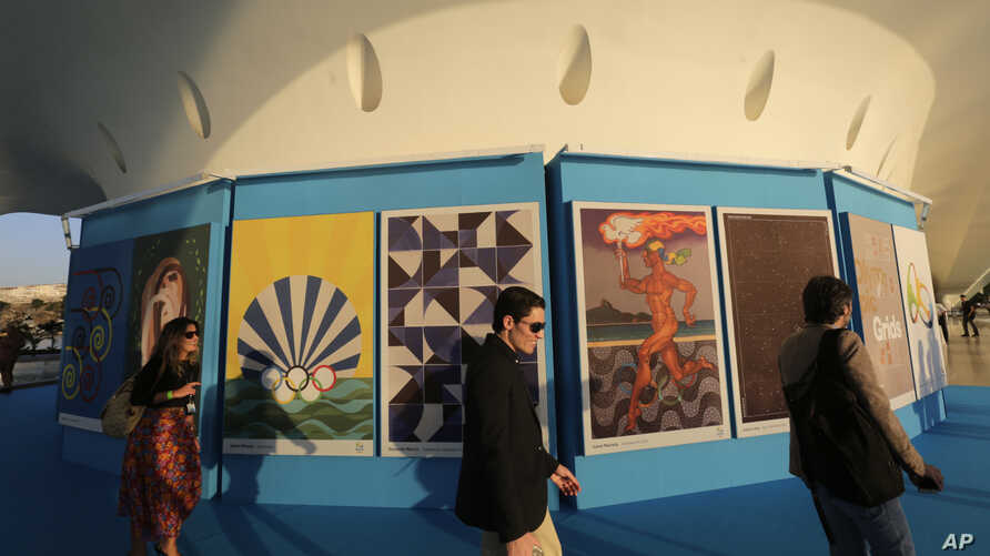 Onlookers walk by a collection of Olympic posters made by 12 Brazilian artists and a Colombian, on display at the Museum of Tomorrow in Rio de Janeiro, Brazil, July 12, 2016. Olympics organizers unveiled a collection of 13 official Olympics posters,