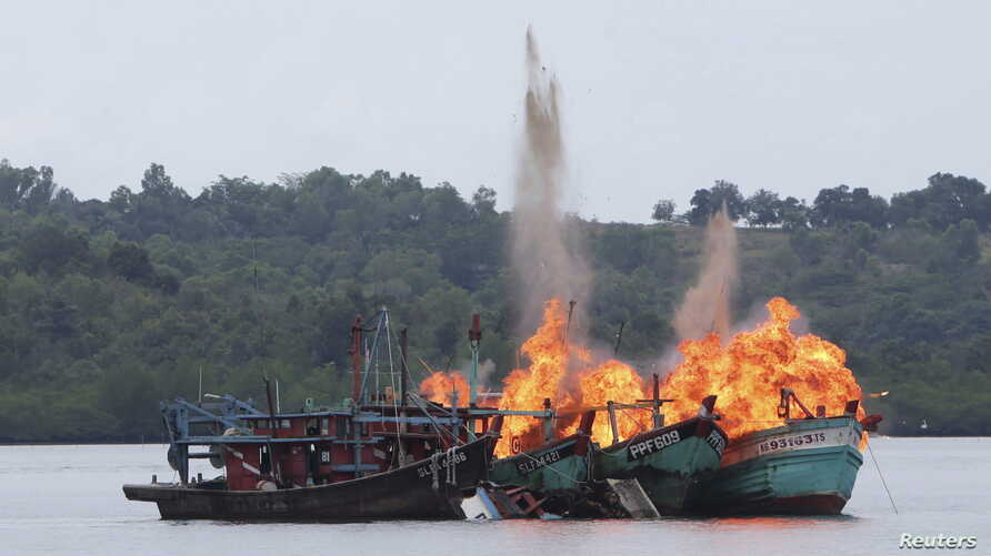 FILE - Malaysian and Vietnamese fishing boats are destroyed for illegal fishing by the Ministry of Maritime Affairs and Fisheries, police and navy, in Batam, Riau Islands, Indonesia, April 5, 2016. The Indonesian government reportedly sank 28 illegal