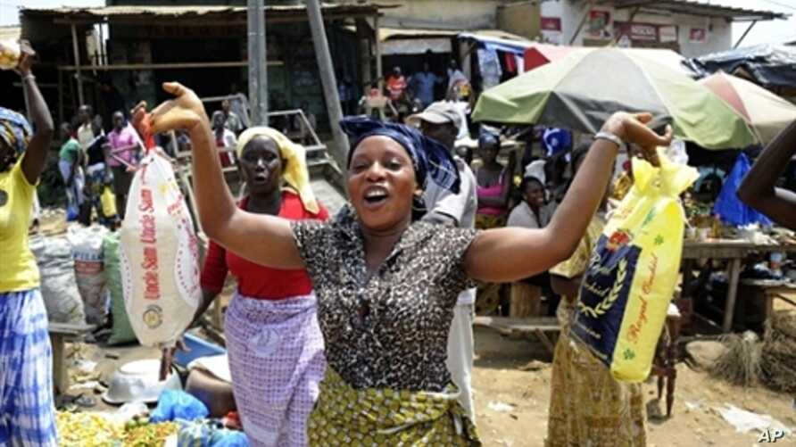 A woman holds bags of rice at a market in Abidjan on April 14, 2011