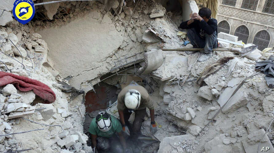 Photo, provided by the Syrian Civil Defense group known as the White Helmets, shows Civil Defense workers from the White Helmets digging in the rubles to remove bodies and look for survivors, after airstrikes hit the Bustan al-Basha neighborhood in A...