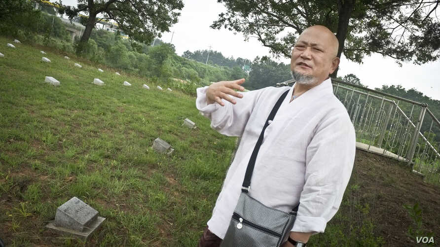 Muk-gai, 56, a South Korean Buddhist monk, at a graveyard for North Koreans and Chinese. Once a month Muk-gai goes to the cemetery to care for the souls of the fallen soldiers by chanting to relieve the suffering of their spirits, Paju, South Korea.