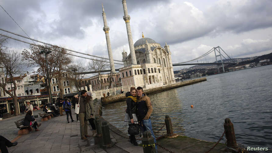 Couples pose for souvenir pictures in front of the Ottoman-era Ortakoy Mecidiye mosque by the Bosphorus strait in Istanbul, Turkey, Jan. 5, 2015.