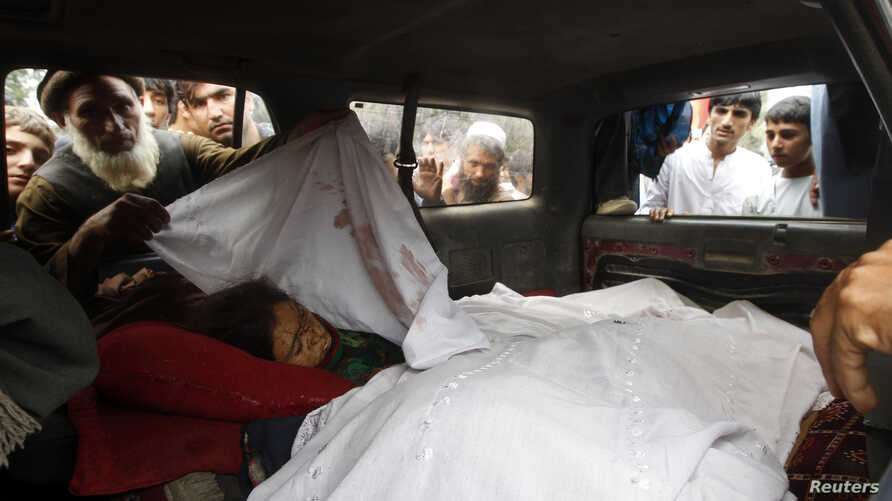 Afghan villagers look at the bodies of women killed by NATO air strikes in Laghman province September 16, 2012.