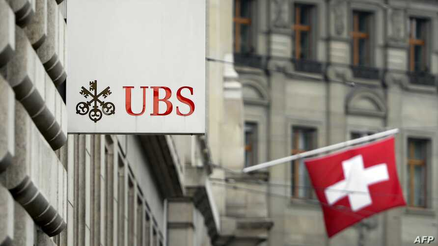 A Swiss flag is seen behind a sign of Swiss bank giant UBS on June 11, 2013 in Basel, Switzerland.