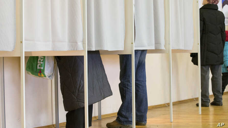 FILE - People fill their ballot papers in voting booths at a polling station in Tallinn, Estonia, March 1, 2015. Estonia has moved away from traditional balloting, with online voting under way for next month's general election, amid tight protective