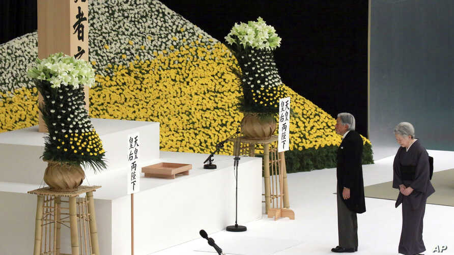 Japan's Emperor Akihito, accompanied by Empress Michiko, walks to deliver his remarks in front of the main altar during a memorial service for the war dead at Nippon Budokan martial arts hall Wednesday, Aug. 15, 2018, in Tokyo.