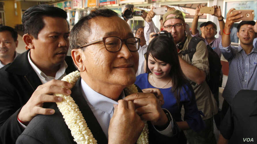 FILE - Sam Rainsy, foreground, leader of the opposition Cambodia National Rescue Party (CNRP), receives a garland of jasmine upon his arrival at Phnom Penh International Airport in Phnom Penh, Cambodia, Aug. 16, 2015.