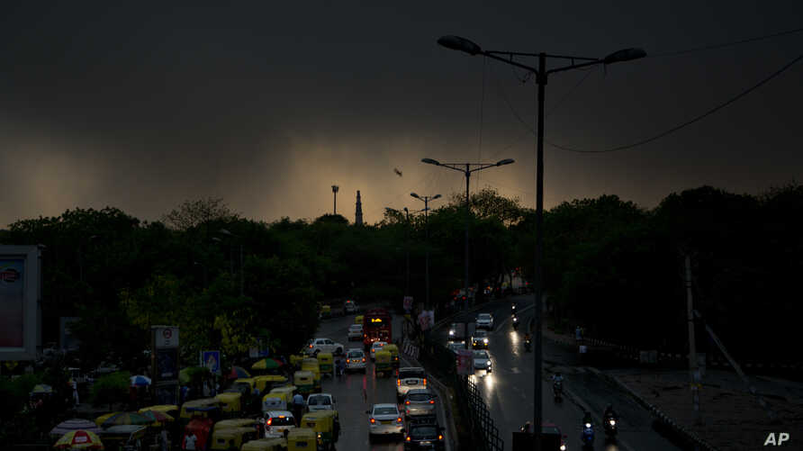 The Qutab Minar monument is silhouetted against a dark cloud covered skyline following a thunderstorm in New Delhi, India, May 13, 2018.