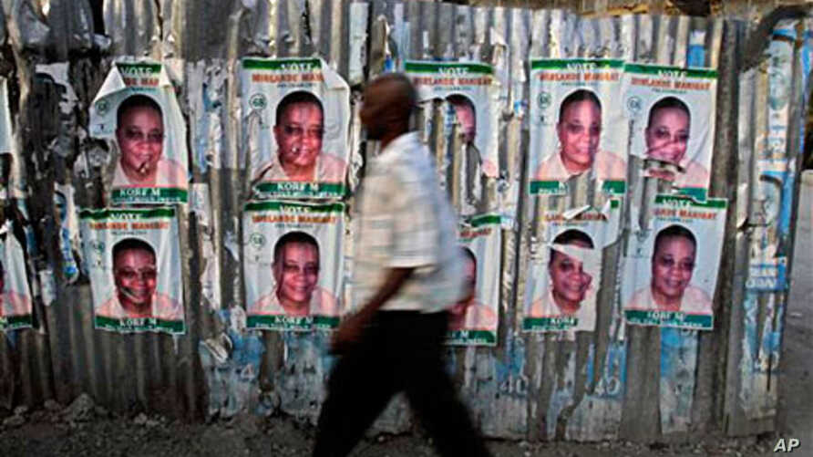 A man walks past a fence covered with election posters in Port-au-Prince, Haiti, Mar 16 2011