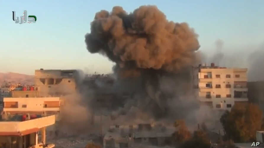 In this image taken from video obtained from the Shaam News Network, which has been authenticated based on its contents and other AP reporting, smoke billows amid buildings at a bomb explosion in Daraya, a countryside of Damscus, Syria, Oct. 15, 2013
