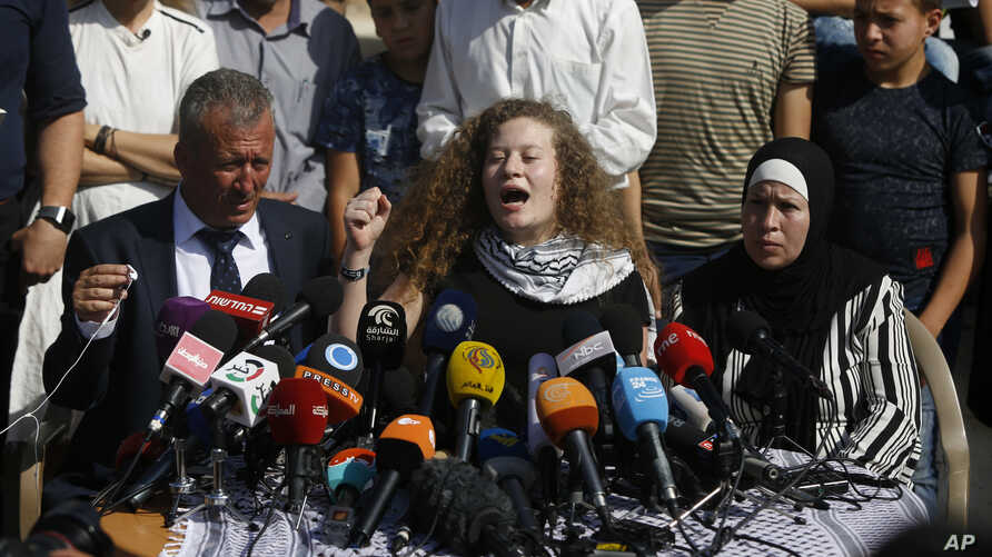 Ahed Tamimi speaks sitting between her father Bassam and mother Nariman during a press conference on the outskirts of the West Bank village of Nabi Saleh near the West Bank city of Ramallah, July 29, 2018.