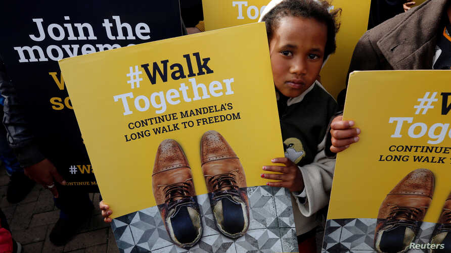 A child holds a placard during a walk to commemorate what would have been Nelson Mandela's 99th birthday in Cape Town, South Africa, July 18, 2017.