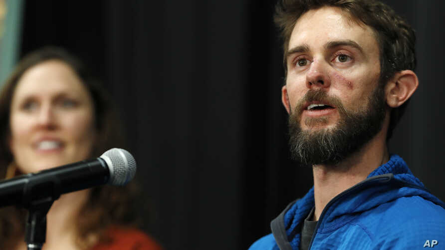Travis Kauffman responds to questions during a news conference in Fort Collins, Colo., Feb. 14, 2019, about his encounter with a mountain lion while running a trail just west of Fort Collins last week. Kaufman's girlfriend, Annie Bierbower, looks on