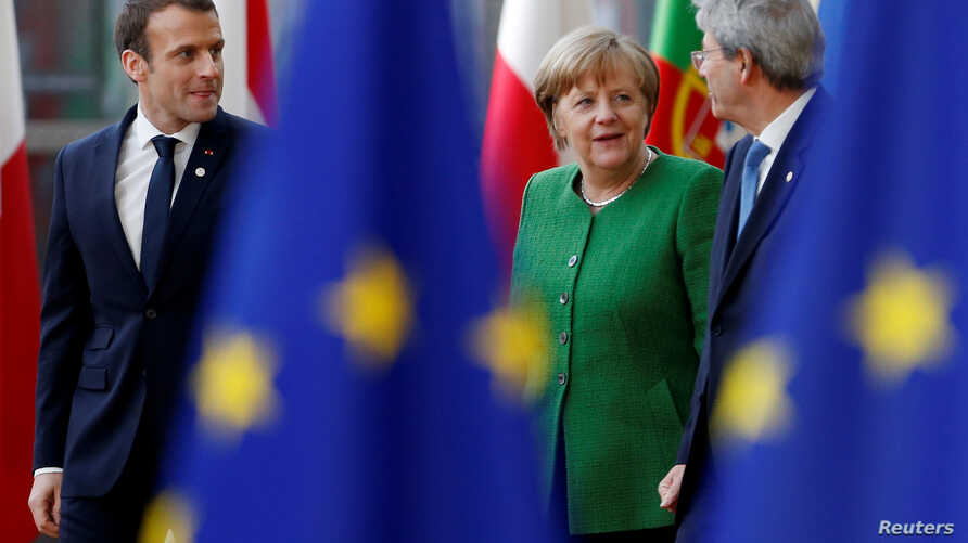 French President Emmanuel Macron, Germany's Chancellor Angela Merkel and Italy's Prime Minister Paolo Gentiloni arrive at a European Union heads of state informal meeting in Brussels, Belgium, Feb. 23, 2018.