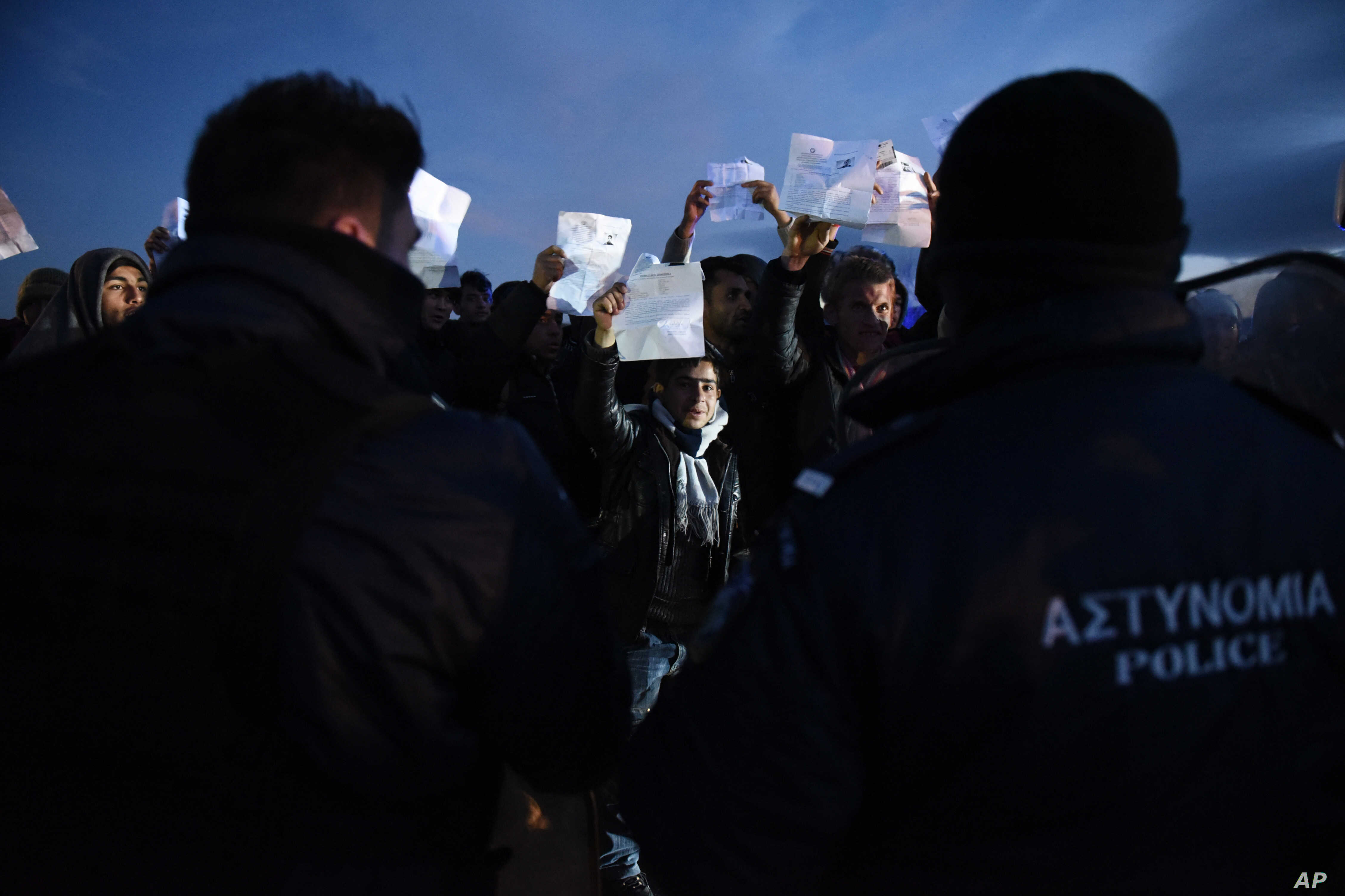 Afghan refugees stage a rally demanding to be allowed by the Greek police to reach the borderline with Macedonia, near the northern Greek village of Idomeni, on Sunday, Feb. 21, 2016.