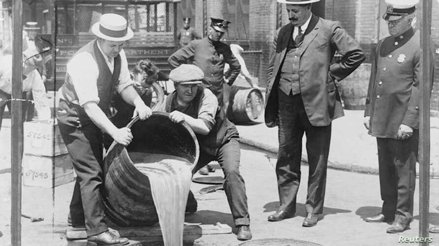 New York City Deputy Police Commissioner John A. Leach (R) watches agents pour liquor into a sewer following a raid during the height of prohibition in an undated photo held by the Library of Congress.