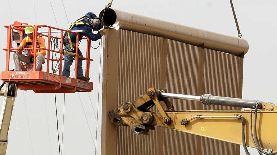 Crews work on a border wall prototype near the border with Tijuana, Mexico, Thursday, Oct. 19, 2017, in San Diego. Companies are nearing an Oct. 26 deadline to finish building eight prototypes of President Donald Trump's proposed border wall with Mex