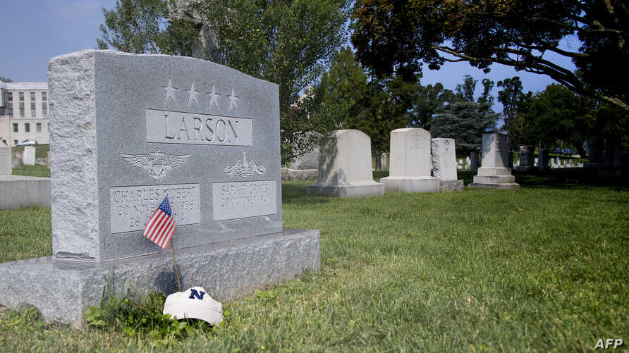 """A flag is placed at the base of the tombstone of U.S. Navy Admiral Charles """"Chuck"""" Larson at the U.S. Naval Academy in Annapolis, Md., on Aug. 24, 2018, near where U.S. Sen. John McCain will be buried on Sept. 2, 2018."""