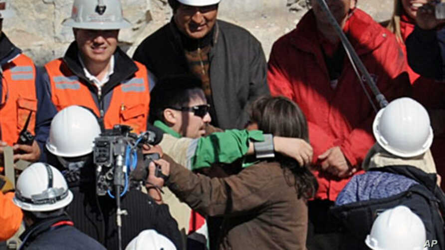 Chilean miner Edison Pena (C) hugs his wife after being brought to the surface, 13 Oct 2010 following a 10-week ordeal in the collapsed San Jose mine, near Copiapo, north of Santiago