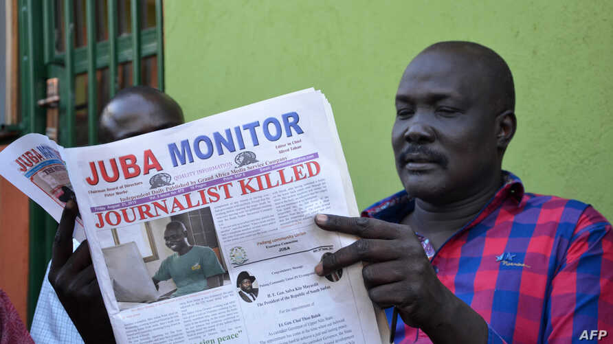 FILE - A man reads a copy of the Juba Monitor, with a heading referring to the killing of South Sudanese journalist Peter Moi of The New Nation newspaper, on August 21, 2015 in Juba.