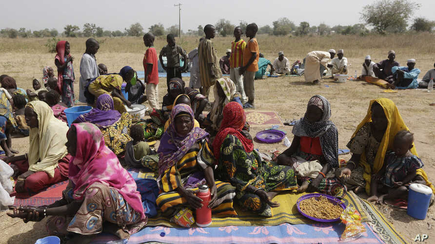 FILE - People displaced by Boko Haram wait to be screened at Furore camp in Yola, Nigeria, near the country's border with Cameroon, Dec. 8, 2015. Returnees to Cameroon have have been rejected by their communities.