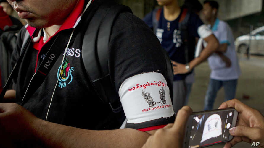 FILE - A local journalist wears an arm band supporting press freedom as he gathers with other journalists during the court appearance of a newspaper editor and a columnist at a township court.