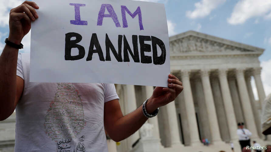 FILE - Mehrad Ansari of Iran holds a sign outside of the U.S. Supreme Court after U.S. President Trump's travel ban was upheld in Washington, June 26, 2018.
