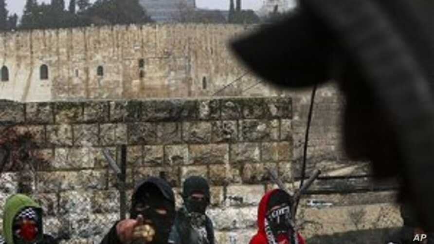 Masked Palestinian youths prepare to throw stones and firecrackers at Israeli police, not seen, as they are backdropped by the Dome of the Rock Mosque, during clashes in the east Jerusalem neighborhood of Ras Al Amud, Sunday, 28 Feb. 2010