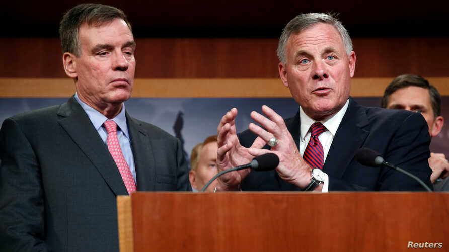 Chairman of the Senate Intelligence Committee Richard Burr (R-NC), right, and the committee's vice chairman Senator Mark Warner (D-VA) speak to the media about the committee's findings and recommendations on threats to election infrastructure on Capi