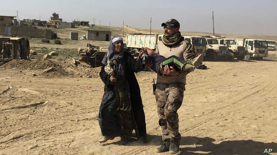 An Iraqi Army soldier helps displaced civilians as they flee their homes due to fighting between Iraqi security forces and Islamic State militants, on the western side of Mosul, Iraq, Tuesday, Feb. 28. 2017.
